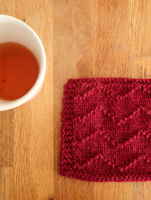 Wave Stitch knitting stitch for beginners. This red textured easy knit stitch features a chevron pattern, and is laying on a wooden table next to a mug of tea.