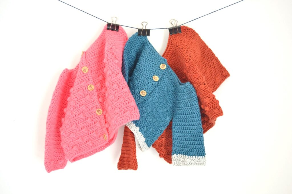 3 bubbly baby cardigans hanging