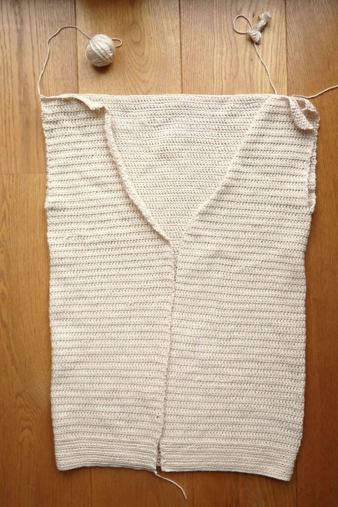 Fold the cardigan body to sew the top and form the armholes